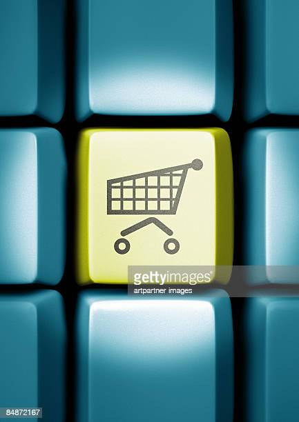 shopping cart on a computer keyboard - consumerism stock illustrations