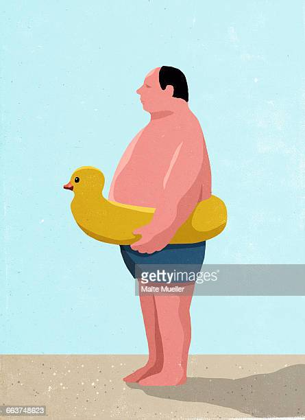 Side view of man wearing inflatable rubber duck ring at beach