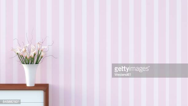 Sideboard with flower vase in front of striped pink wallpaper
