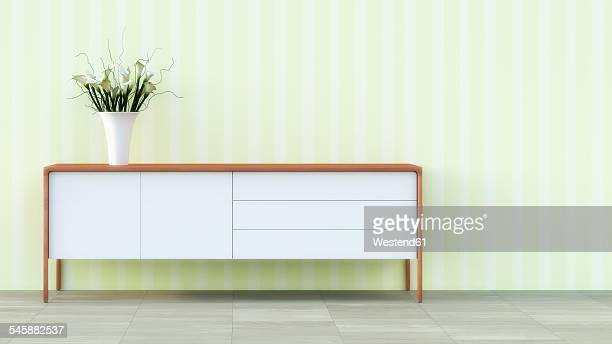 Sideboard with flower vase in front of striped wallpaper