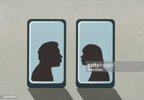 stockillustraties, clipart, cartoons en iconen met silhouette couple kissing on separate smart phone screens - dating