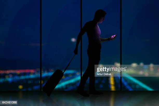 Silhouette of a guy checking his smartphone ready to departure on a airport at night with bokeh lights during a travel with trolley suitcase using application technology to get information about the trip.
