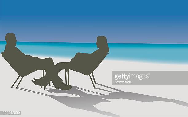Silhouette of a young man and a young woman sitting on the beach and talking