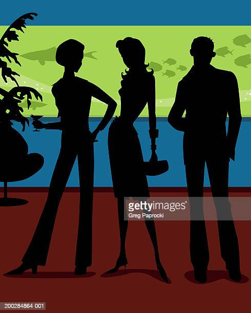 Silhouette of three adults standing in club, aquarium in background