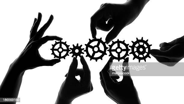 silhouetted hands holding mechanical cogs and gears, teamwork and collaboration concept - order stock illustrations, clip art, cartoons, & icons