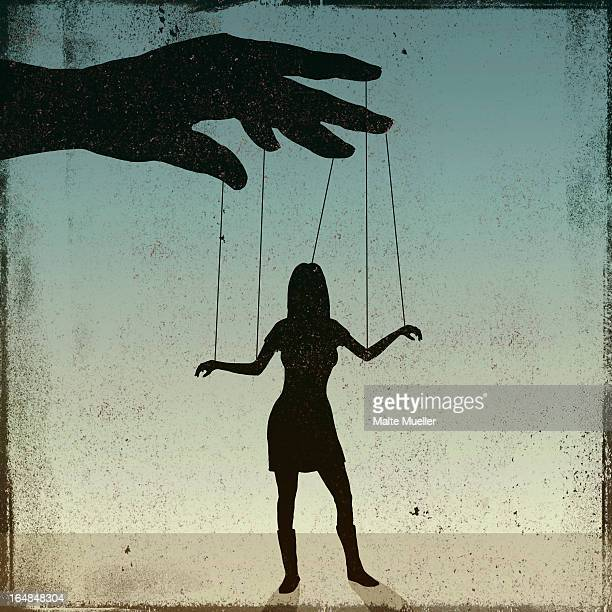 A silhouetted woman being controlled by a puppeteer
