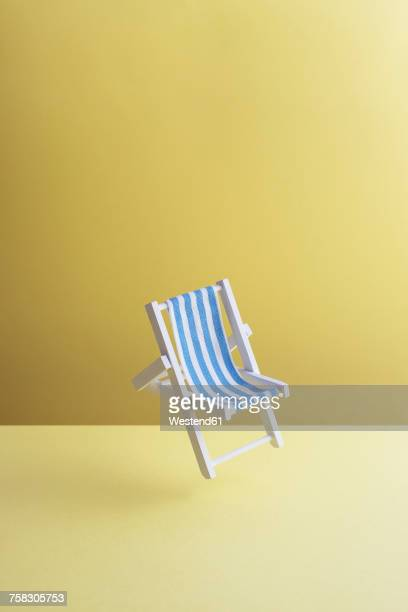 Single beach chair hovering in the air in front of yellow ground, 3D Rendering