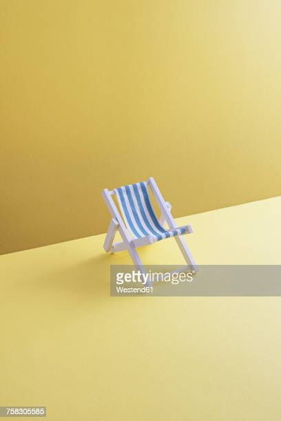 Single beach chair on yellow ground, 3D Rendering