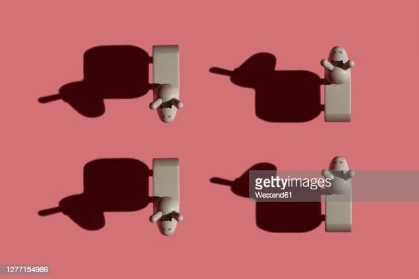 studio shot of four small donkey figurines against pastel red background - four objects stock illustrations