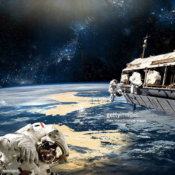 a team of astronauts perform work on a space station while orbiting a large, earth-like planet. the nearby star shines down on the world below.  - milky way stock illustrations