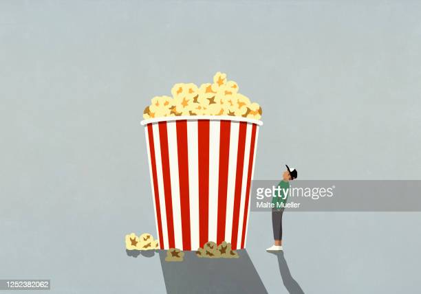 illustrations, cliparts, dessins animés et icônes de teenage boy looking up at large movie theater popcorn tub - jeunes garçons