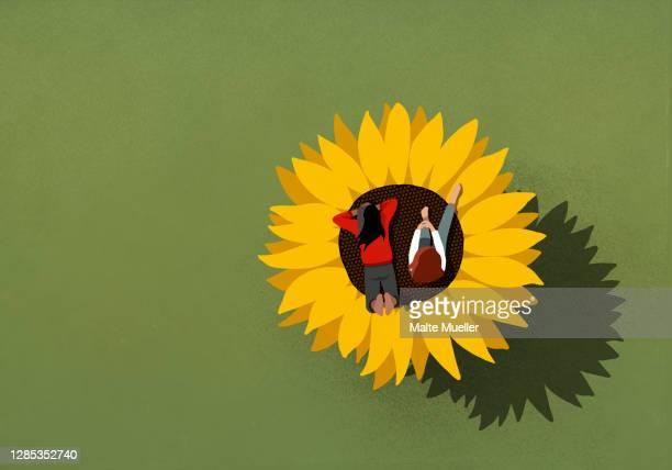 teenage girls relaxing on large sunflower on green background - female friendship stock illustrations