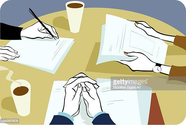 Three executives looking at paperwork in meeting, focus on hands