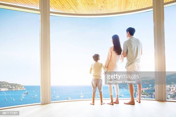 Three members of family looking at the ocean from the inside