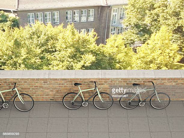 Three racing cycles standing against a wall, 3D Rendering