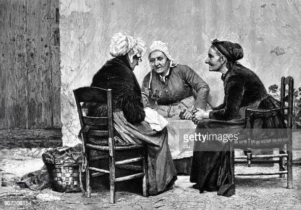 Three senior women sitting together talking gossip