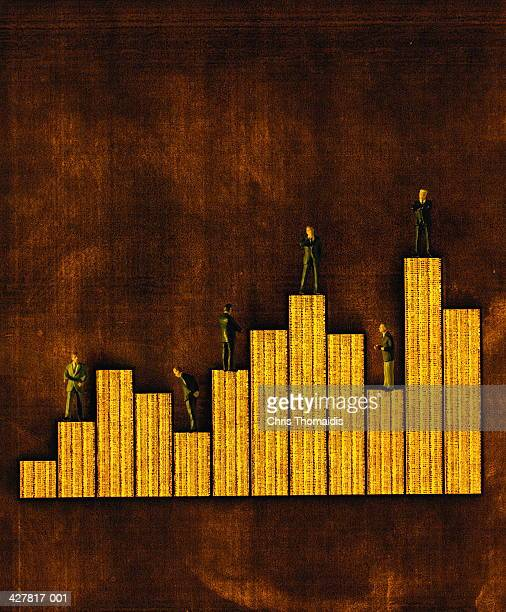 Toy business figures standing on top of bar chart
