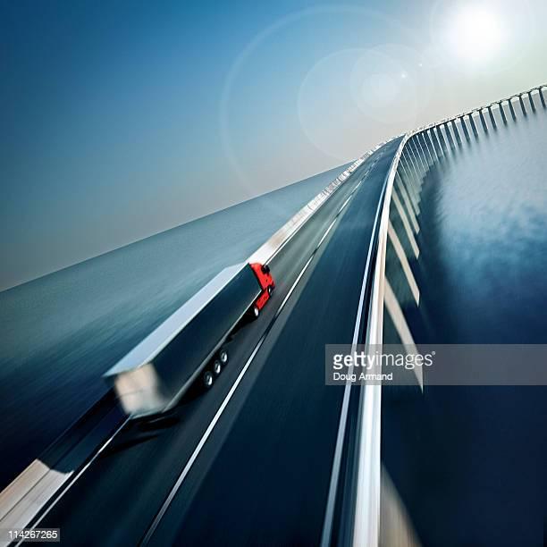 truck on roadway crossing water - horizont stock-grafiken, -clipart, -cartoons und -symbole