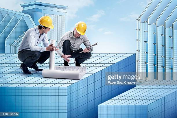 Two architects looking at blue prints