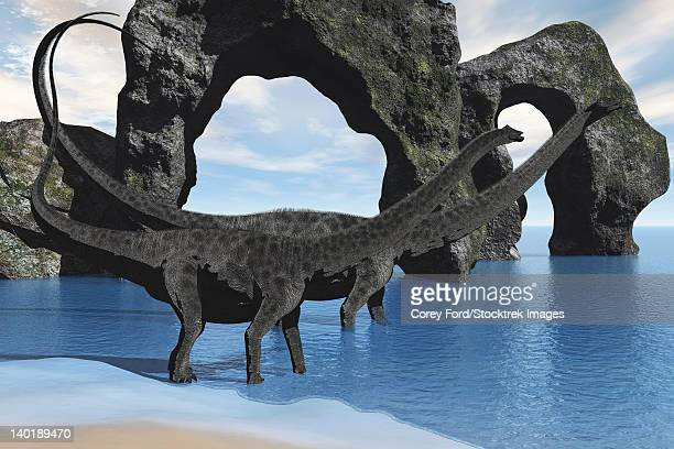 two diplodocus dinosaurs wade through shallow waters of a beautiful seashore. - natural arch stock illustrations, clip art, cartoons, & icons