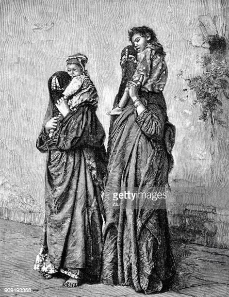 Two Egyptian, fully veiled women, carry their children piggyback