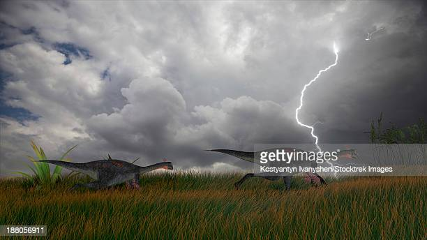 Two Gigantoraptors running across a grassy field during a lightning storm.
