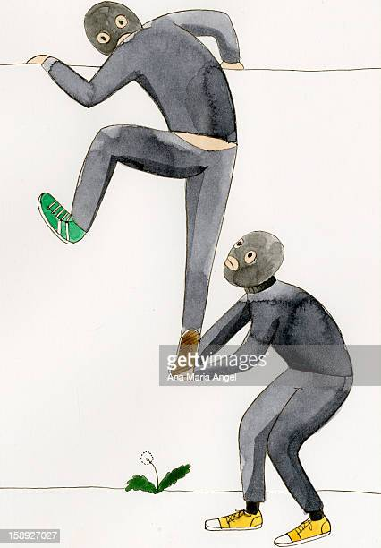 Two masked men climbing a wall