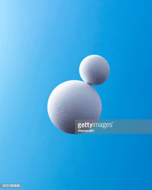 two white spheres in front of blue background - digitally generated image stock illustrations