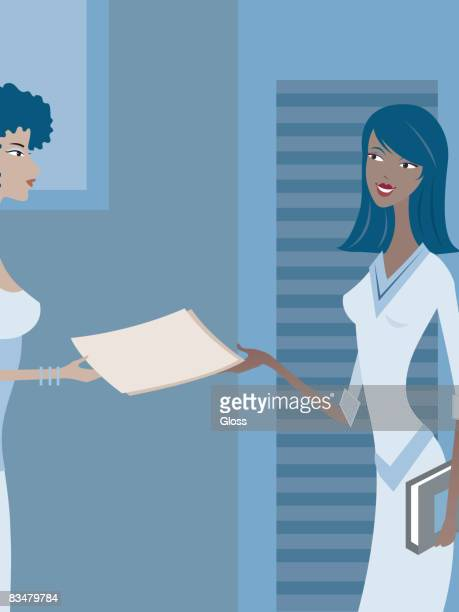 Two women exchanging a file