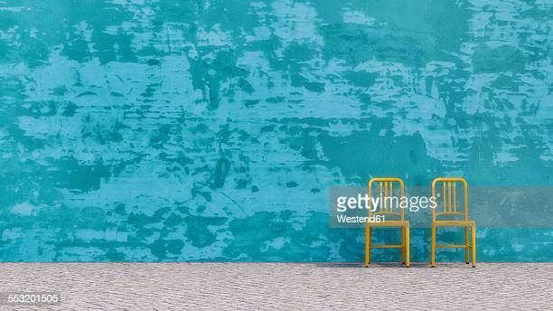 Two yellow chairs standing in front of blue concrete wall, 3D Rendering