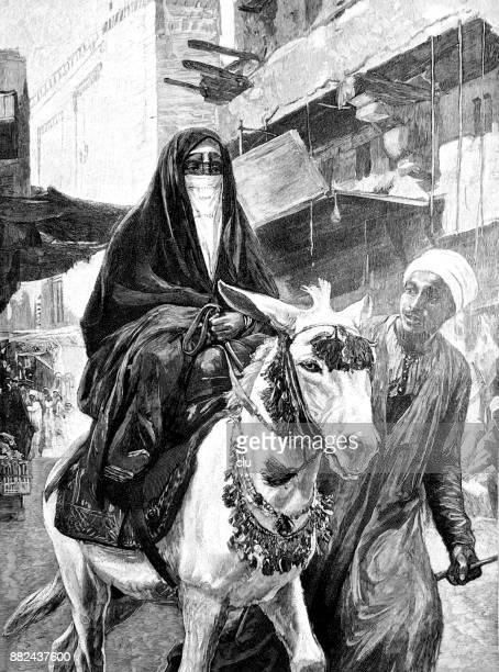 Veiled woman on a donkey with her servant riding through Cairo
