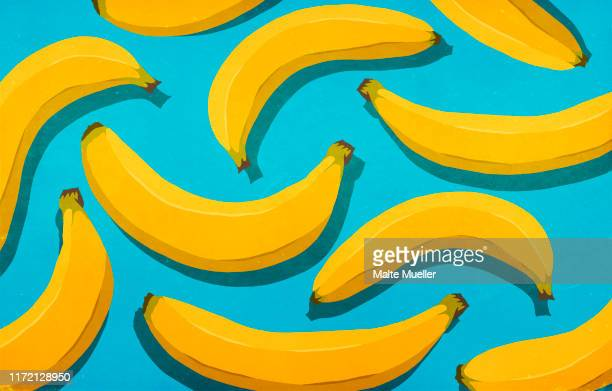ilustraciones, imágenes clip art, dibujos animados e iconos de stock de vibrant, unpeeled yellow bananas on blue background - banana