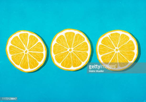 vibrant yellow lemon slices against blue background - food and drink stock illustrations