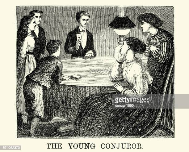 Victorian boy doingh a card trick for his friend and family