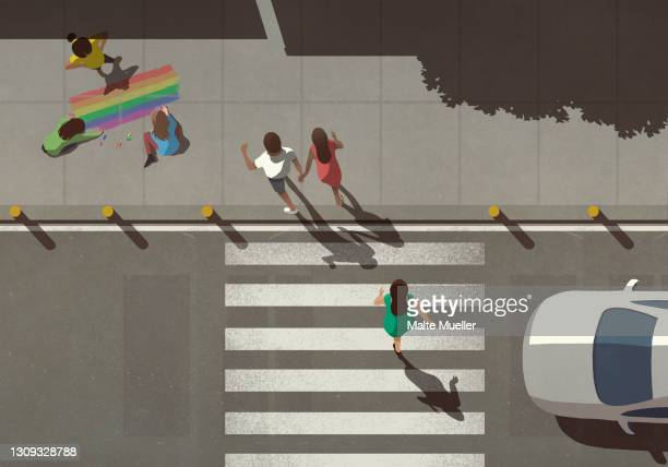 view from above pedestrians crossing street by kids coloring rainbow on sidewalk - road marking stock illustrations
