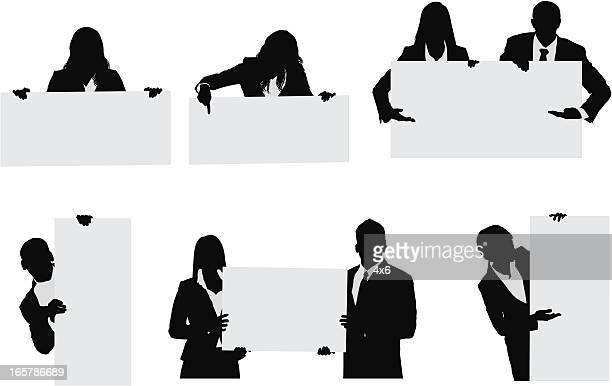 waist up businessmen and businesswomen holding signs - holding up sign stock illustrations