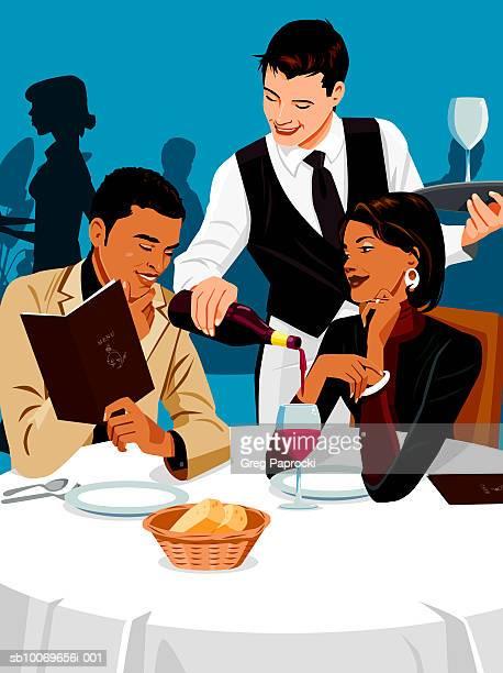 Waiter serving couple in restaurant