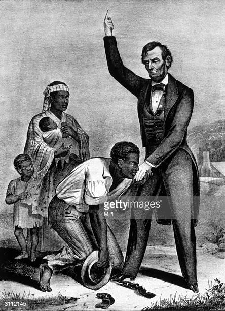 Watched by his family a freed slave his shackles at his feet kisses the hand of President Lincoln