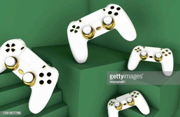 white and gold colored video game consoles on green backround - four objects stock illustrations