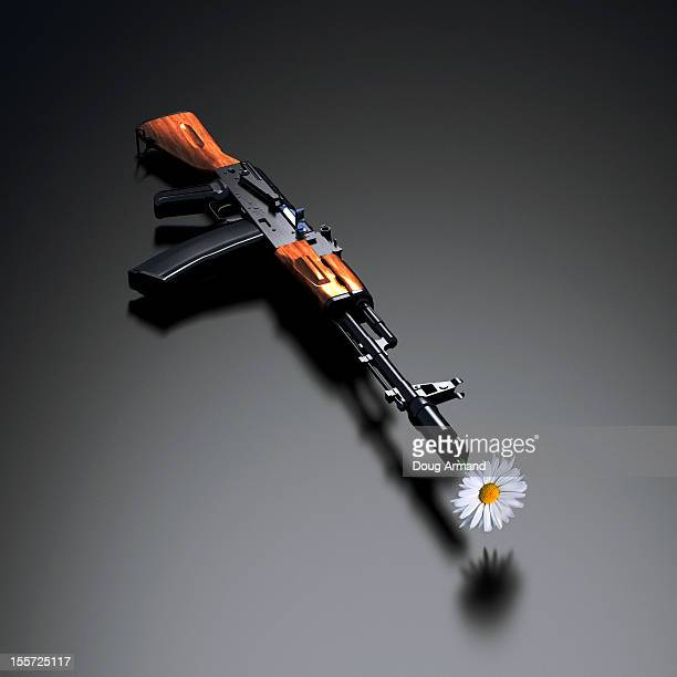 AK-47 with flower in muzzle on shiny surface