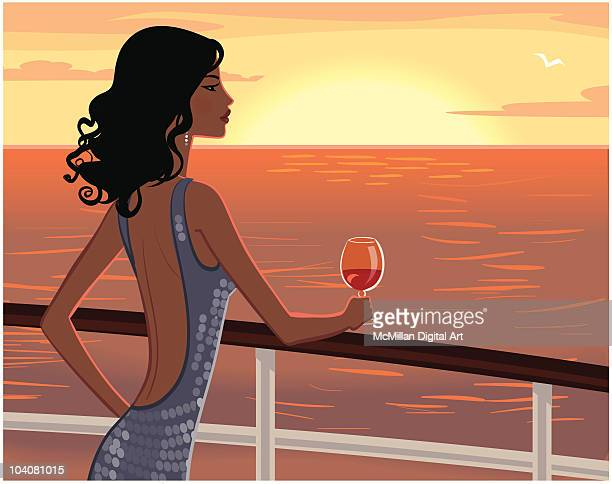 Woman drinking glass of wine at sunset