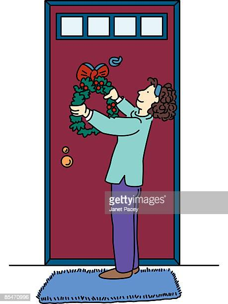 A woman hanging a wreath on her door