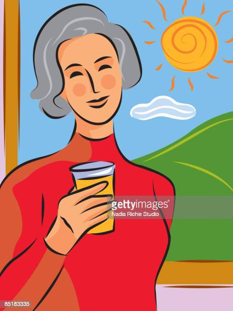 A woman having a glass of orange juice in front of a window