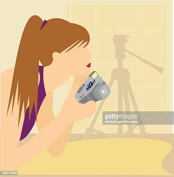 woman holding a camera - camera tripod stock illustrations, clip art, cartoons, & icons
