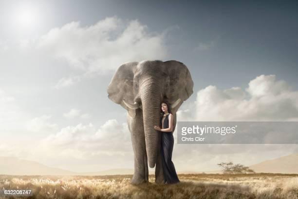 Woman hugging elephant in remote field