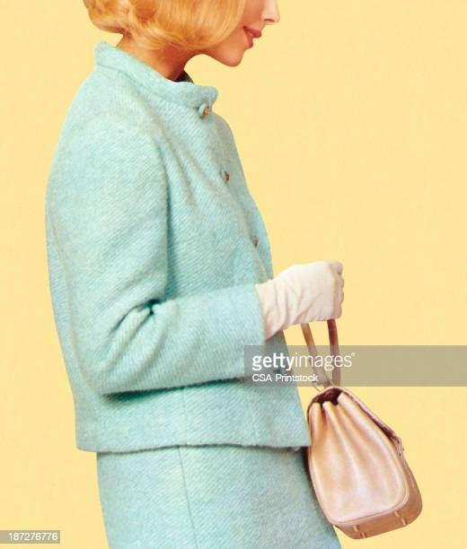 A woman in vintage blue suit holding a purse