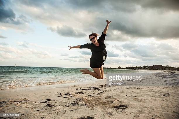 woman jumping on mexico beach - carefree stock illustrations