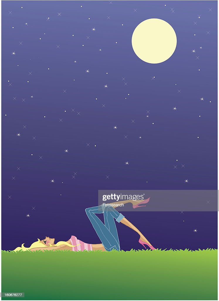 Woman Laying On Grass Looking At The Starry Night Sky stock