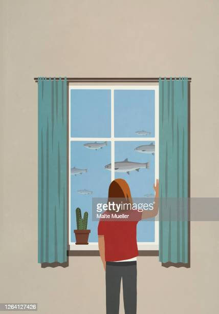 woman looking at swimming fish from window - standing stock illustrations