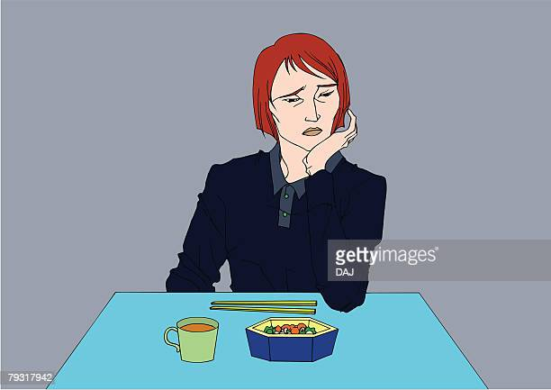 Woman losing appetite and looking away from food on table, unhappy, front view